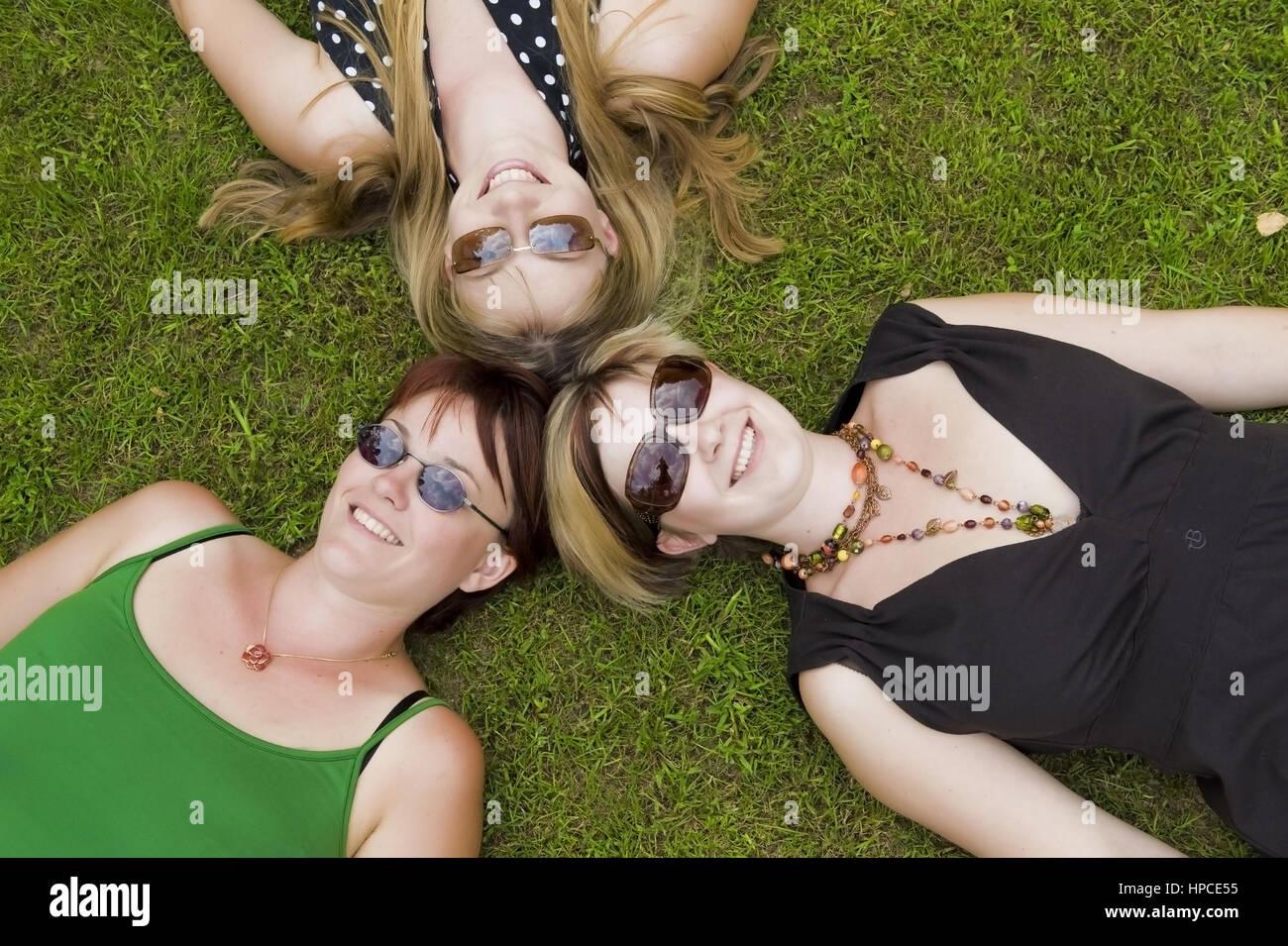 Model released , Drei Frauen mit Sonnenbrillen liegen Kopf an Kopf in der Wiese - women lying in the meadow Stock Photo