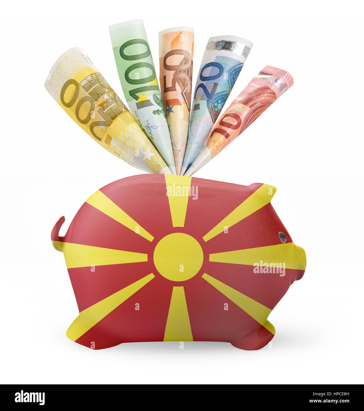 Side view of a piggy bank with the flag design of Macedonia and various european banknotes.(series) - Stock Image