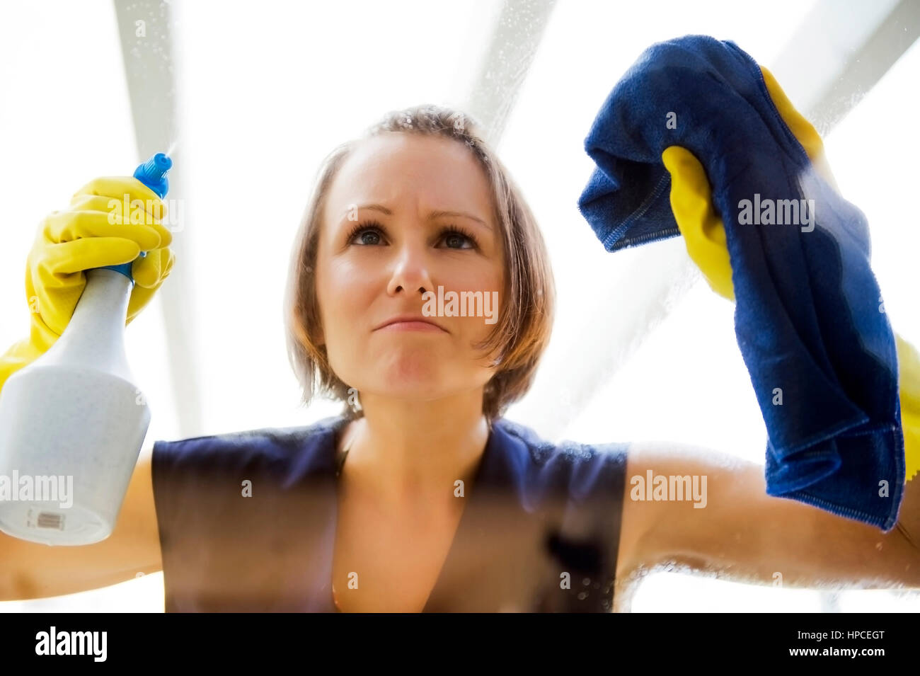 Model released , Junge Putzfrau beim Fensterputzen - woman cleans the window Stock Photo