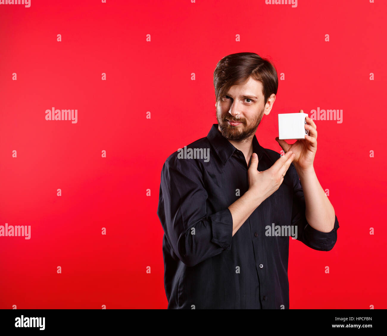 Man holding an empty cube. Advertising Space. Attractive man shows space for copy. Noteworthy. - Stock Image