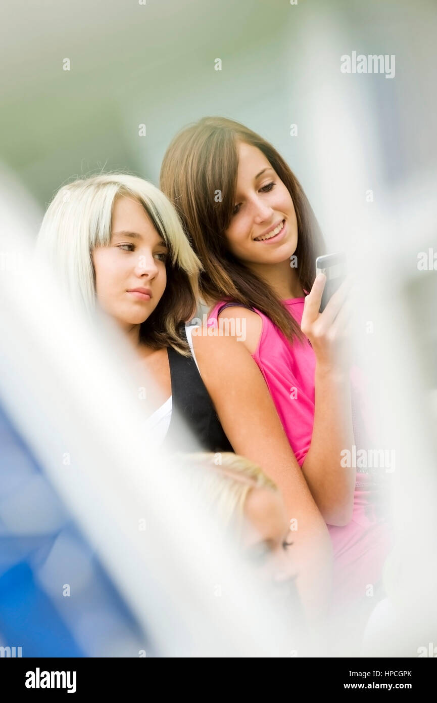Model released , Zwei Maedchen, 13, mit Handy - two girls with mobile phone - Stock Image