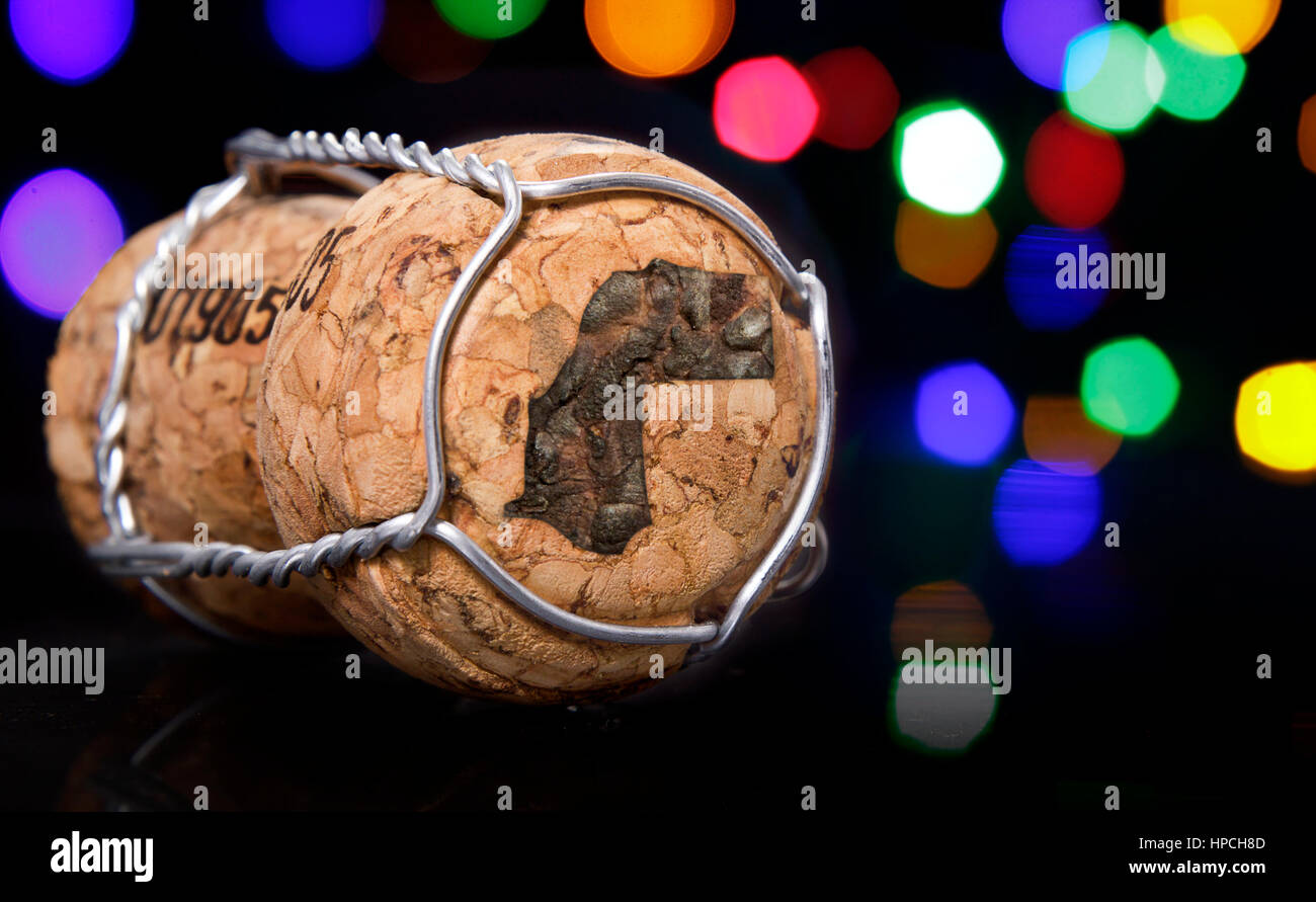 Champagne cork with the shape of Western Sahara burnt in and colorful blurry lights in the background.(series) - Stock Image