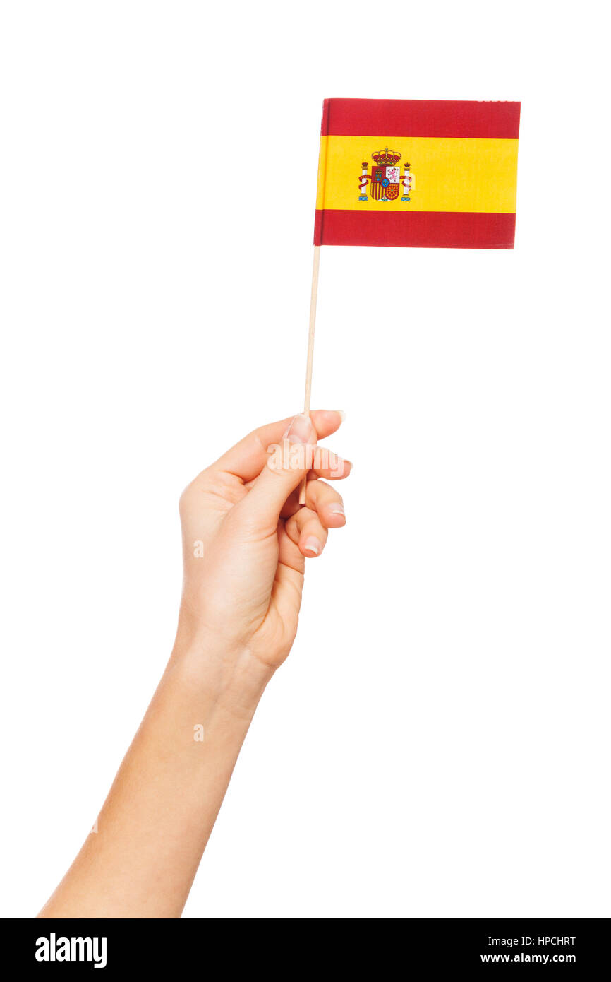 Hand holding the national flag of Spain by flagpole, isolated on white - Stock Image