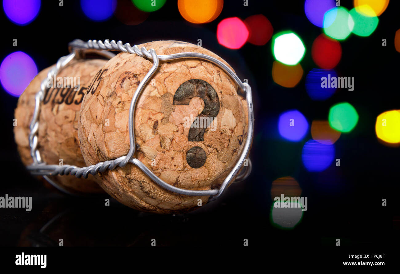 Champagne cork with the shape of a question mark burnt in and colorful blurry lights in the background.(series) - Stock Image