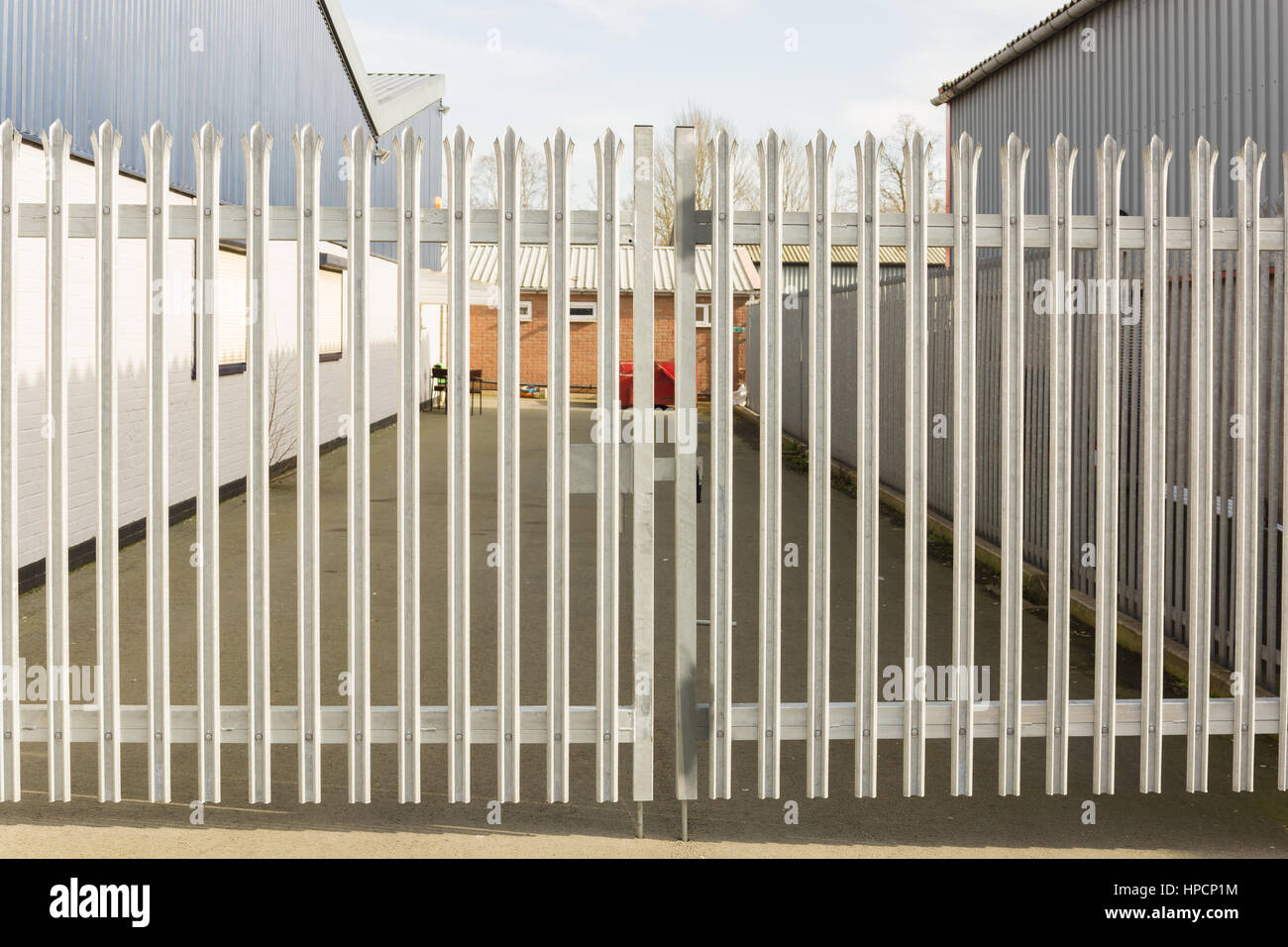 Set of locked spiked security gates at an industrial or commercial premises - Stock Image