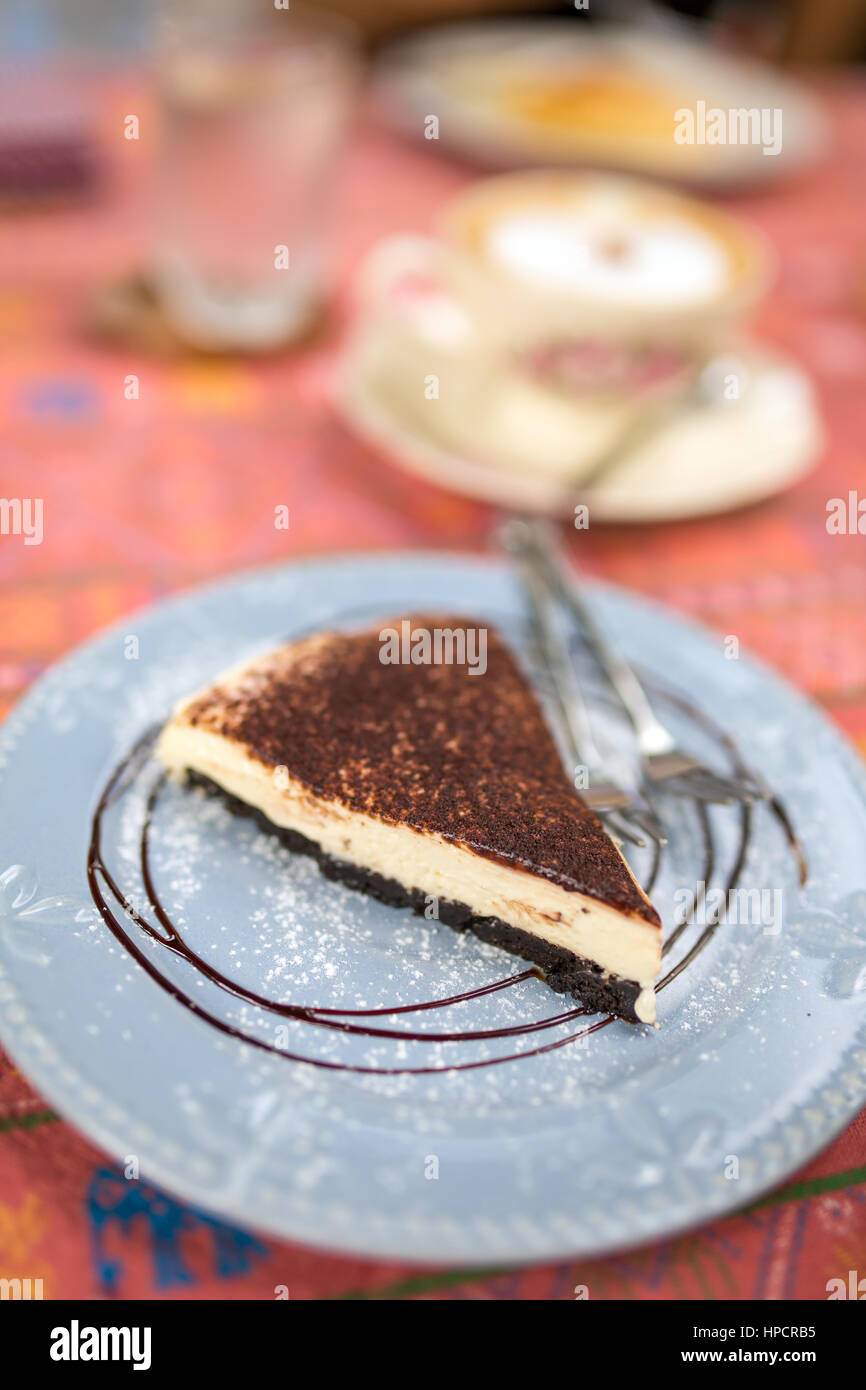 Delicious piece of cheesecake close-up in cafe with low depth of field. - Stock Image