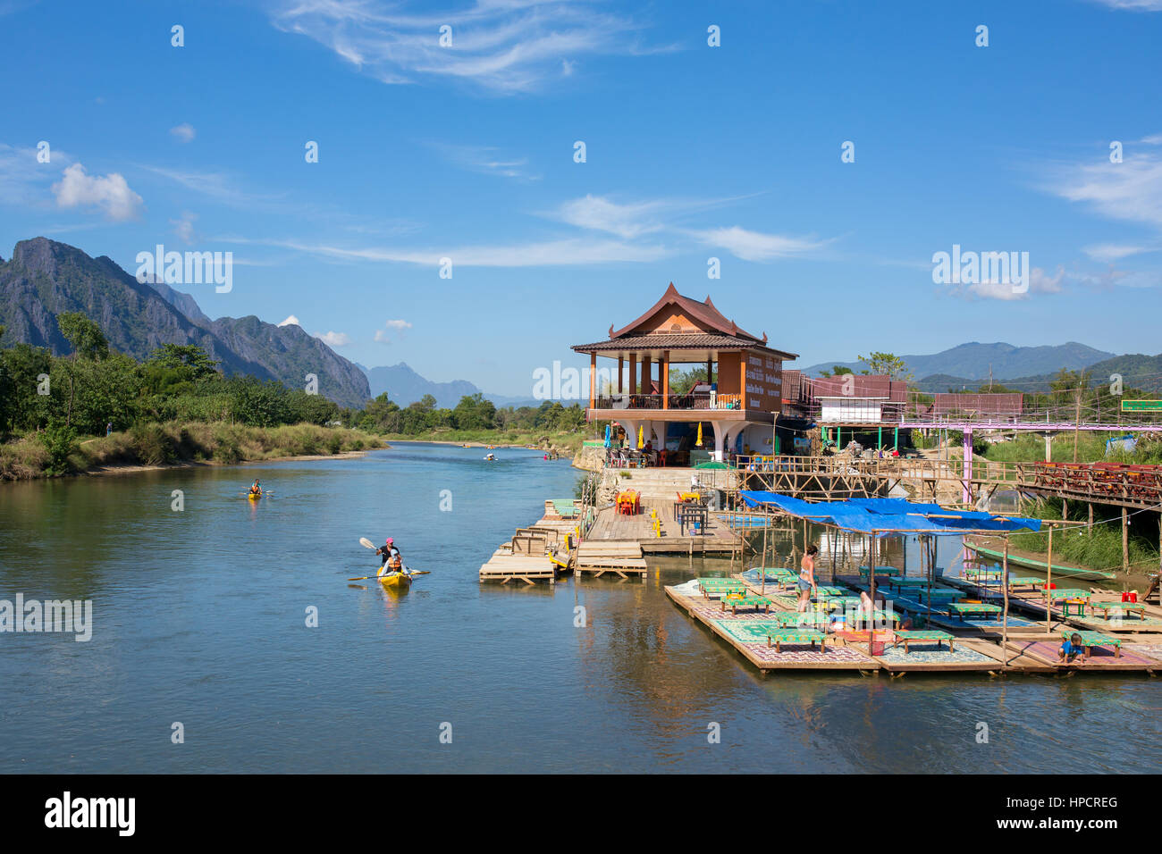 Vang Vieng, Laos - January 19, 2017: Unidentified tourists are rowing kayak boats in Nam Song River in Vang Vieng, - Stock Image