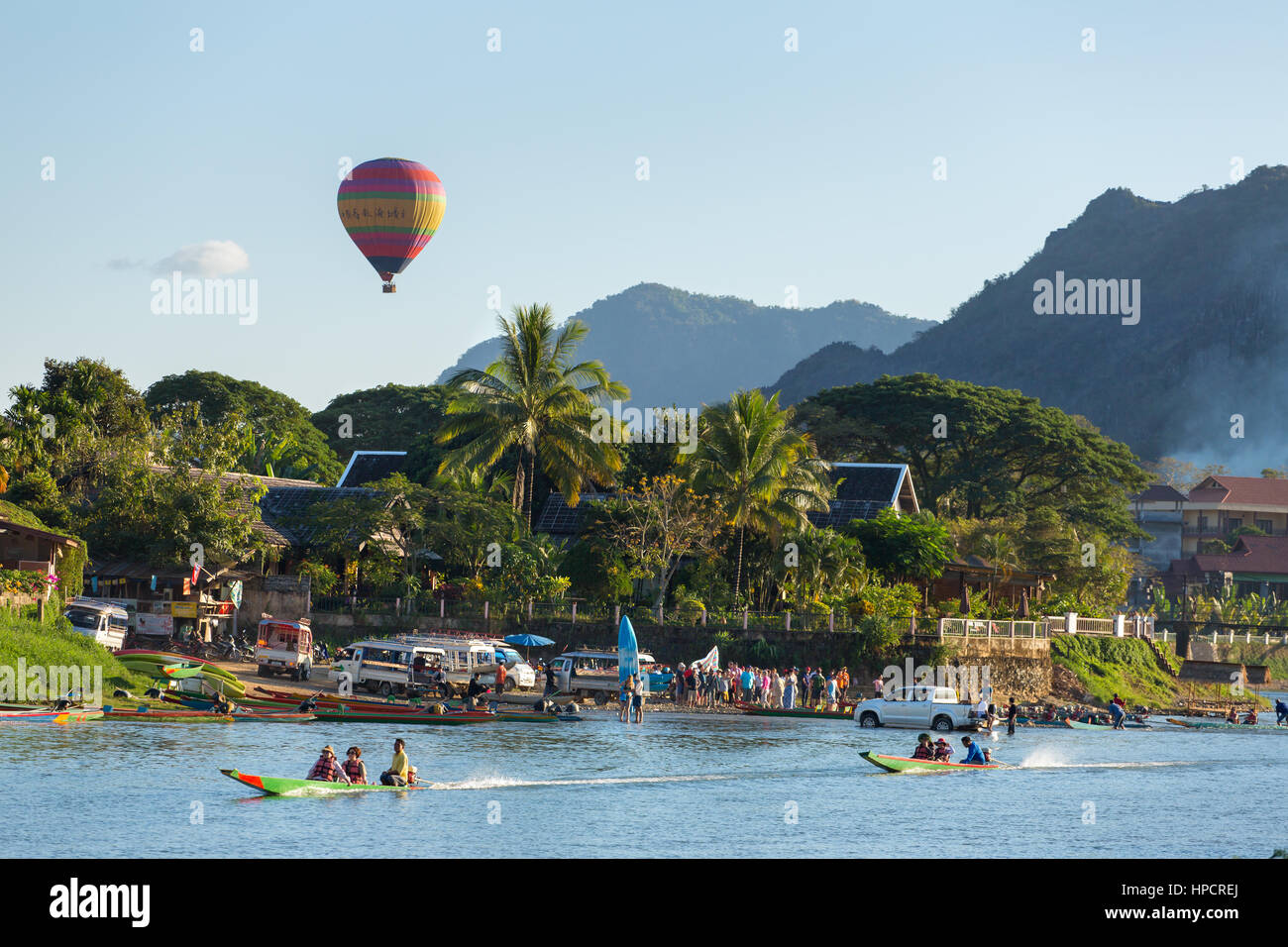 Vang Vieng, Laos - January 19, 2017: Unidentified tourists are riding  speedboats in Vang Vieng village with a hot - Stock Image