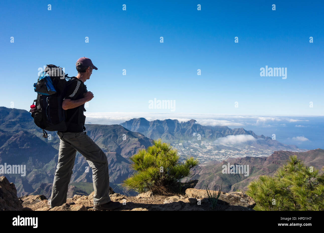 Mature male hiker on Alta Vista mountain on Gran Canaria with La Aldea de San Nicolas village in distance. Canary - Stock Image