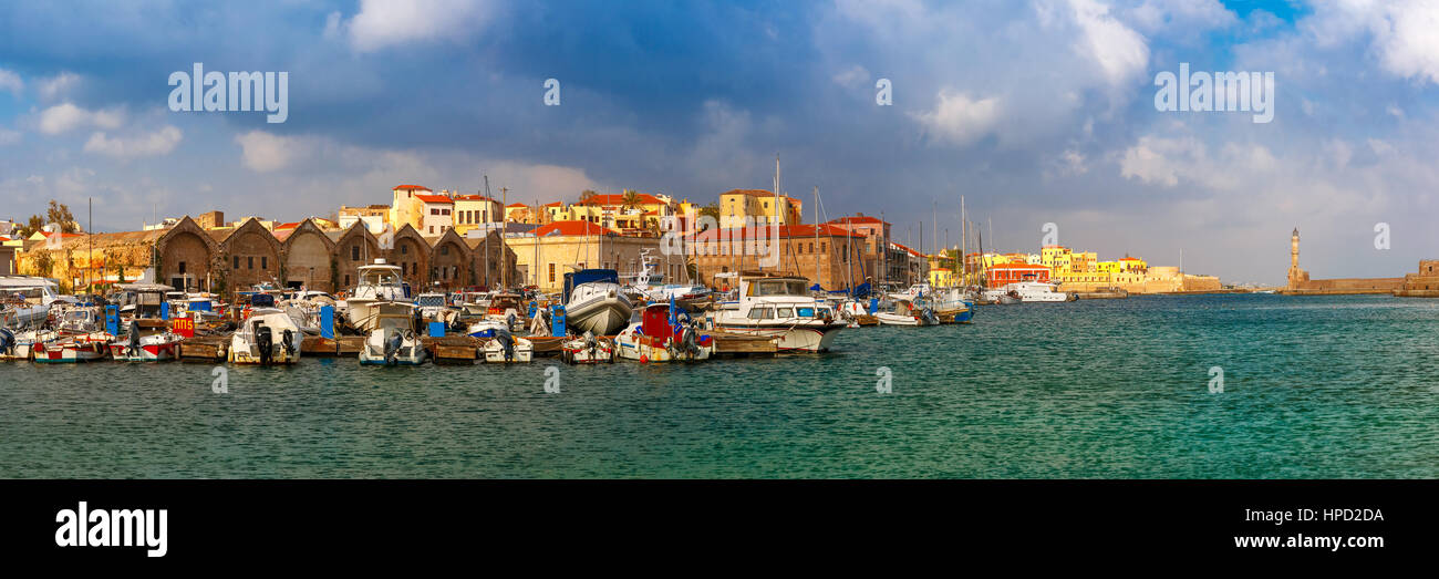 Panorama of Chania Arsenals, the Venetian shipyards, and fishing boats in old harbour of Chania in sunny and cloudy - Stock Image