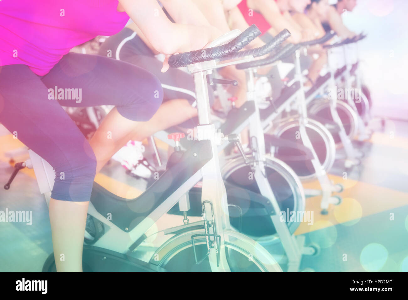 Spin class working out in a row against abstract background - Stock Image