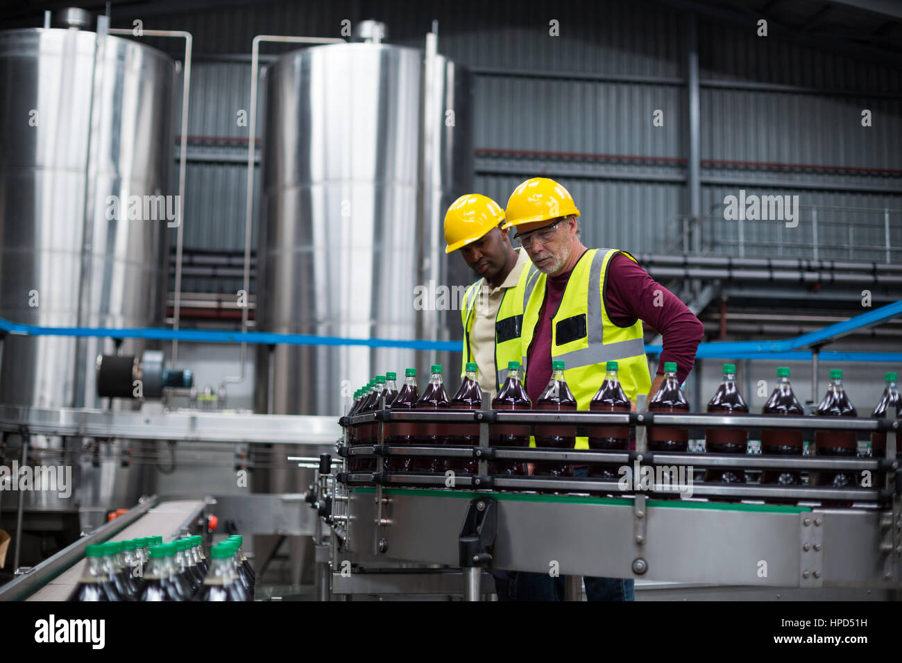 Two factory workers monitoring cold drink bottles at drinks production plant Stock Photo
