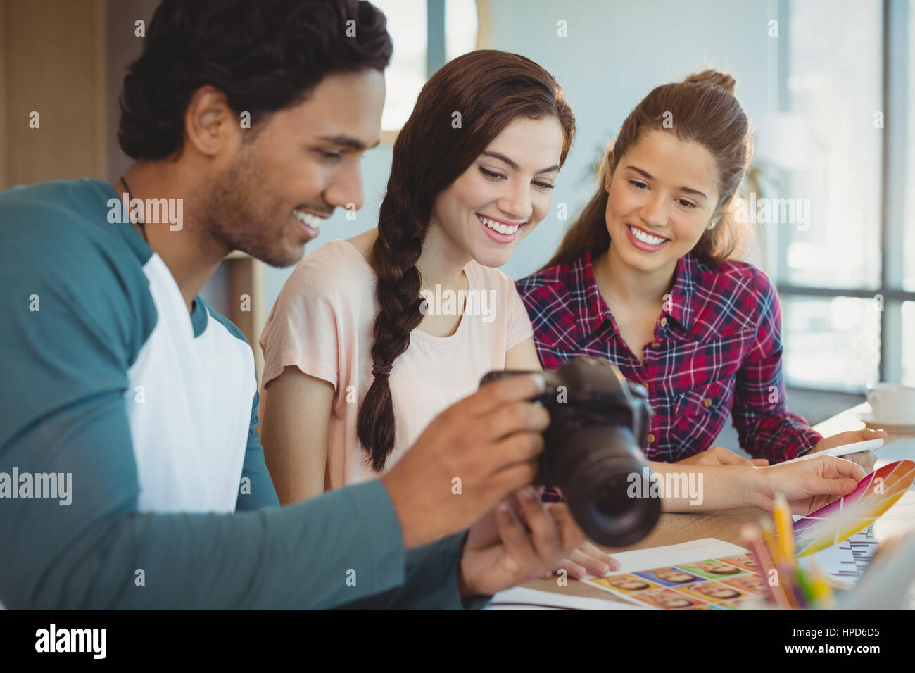 Fashion designers looking at photographs in digital camera at office - Stock Image
