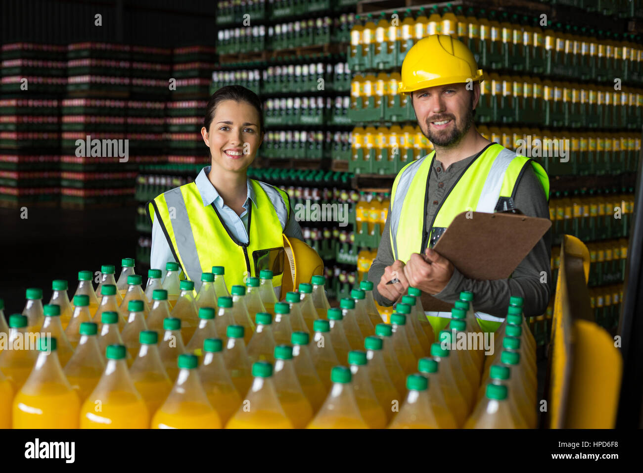 Portrait of two factory workers monitoring cold drink bottles at drinks production factory Stock Photo
