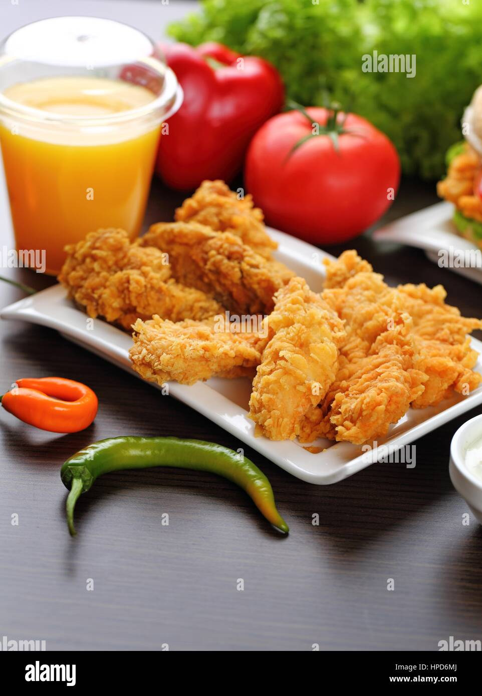 Breaded chicken strips with sauces, tomatoes, peppers. - Stock Image