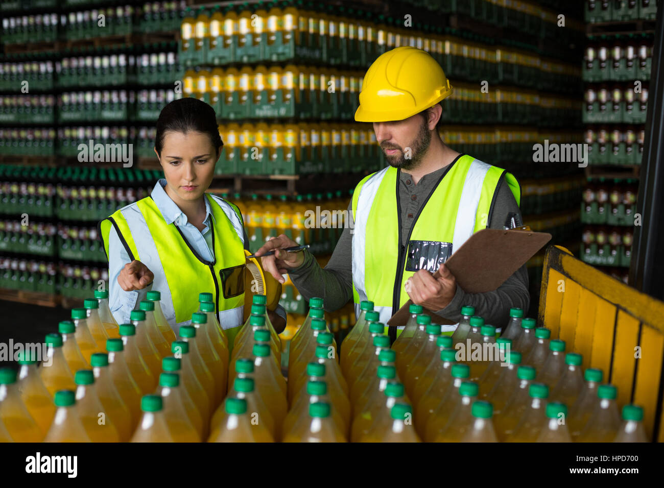 Two factory workers monitoring cold drink bottles at drinks production factory Stock Photo