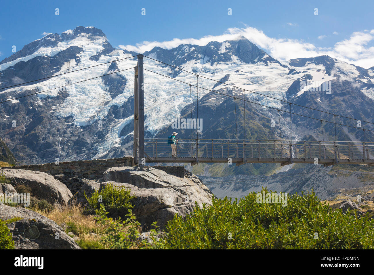 Aoraki/Mount Cook National Park, Canterbury, New Zealand. Hiker crossing suspension bridge on the Hooker Valley - Stock Image