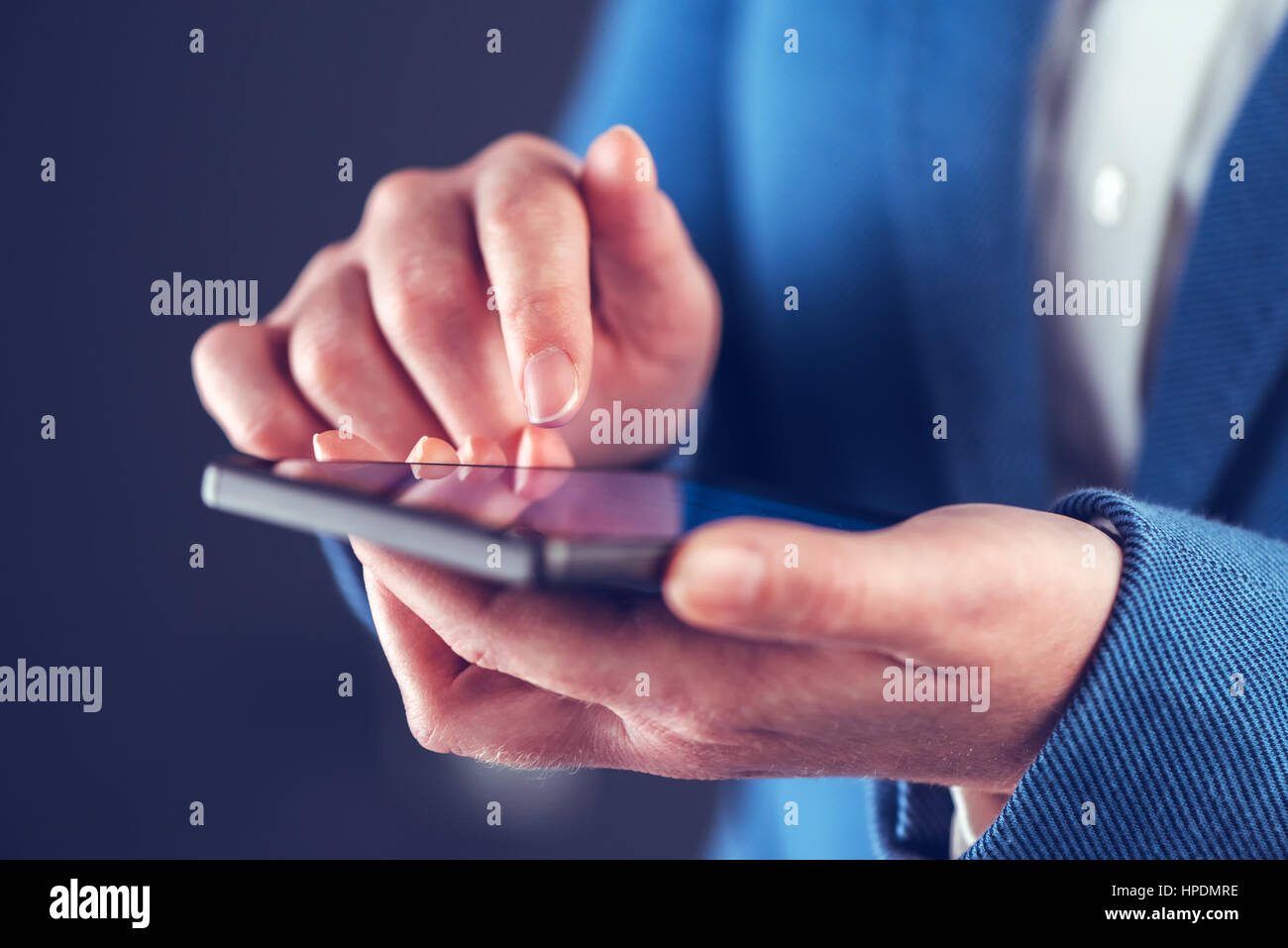 Businesswoman using mobile phone and sending SMS message - Stock Image