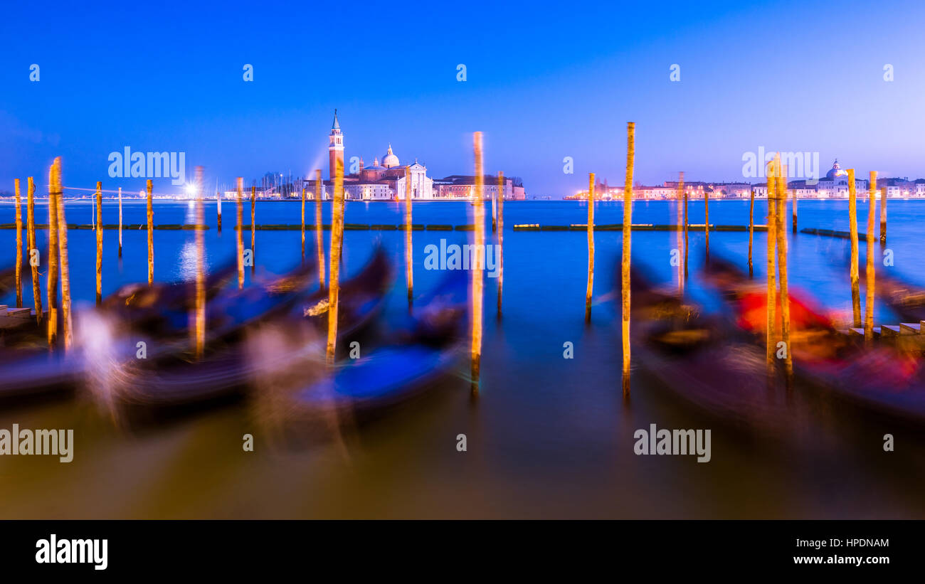 gondolas line the bank at st mark's square in venice during blue hour. The image is a long exposure causing - Stock Image