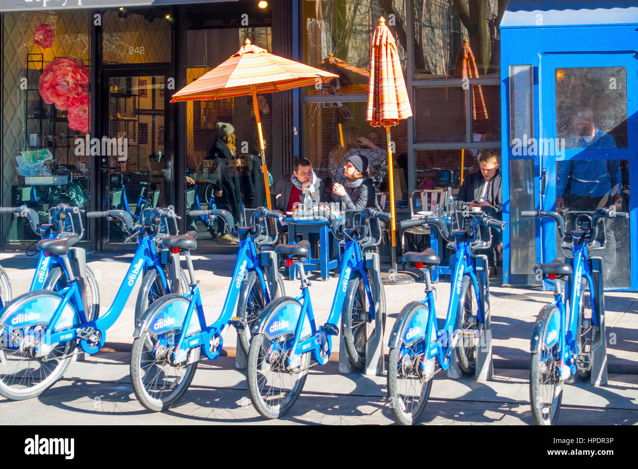 Alfresco diners outside a cafe in winter and a line of Citibike rental bicycles - Stock Image