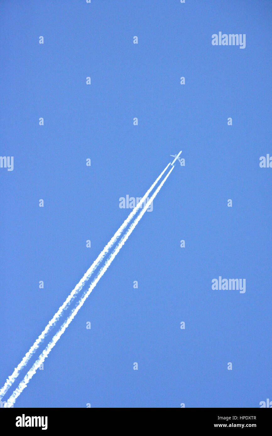 A jet soaring into a cloudless , Summer sky with parallel vapour trails. 'Parallel Lines'.  Abstract, full - Stock Image