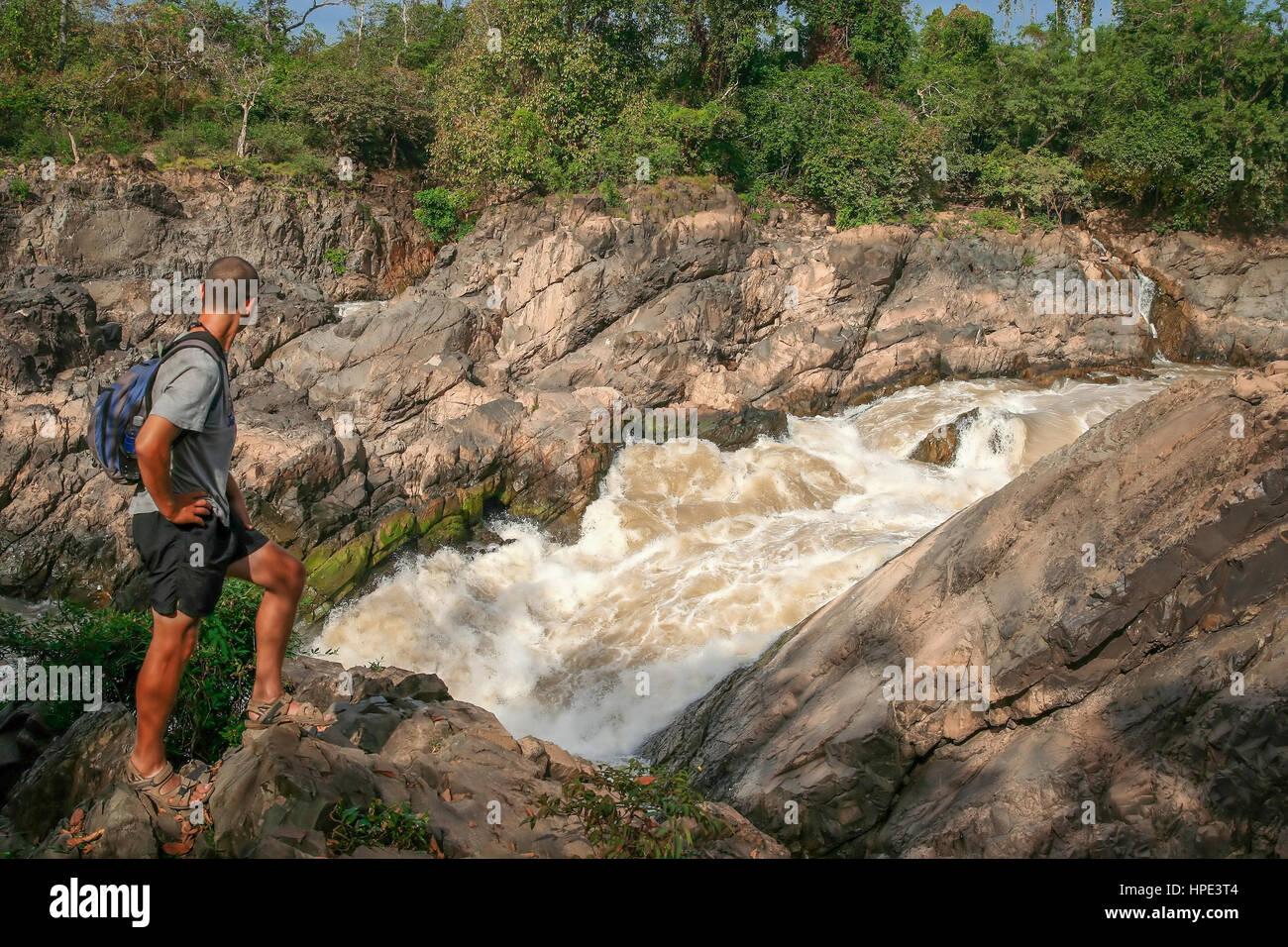 Tourist admiring powerful Don Khon (Khon Phapheng ) waterfall on the Mekong river, Don Det, Laos - Stock Image