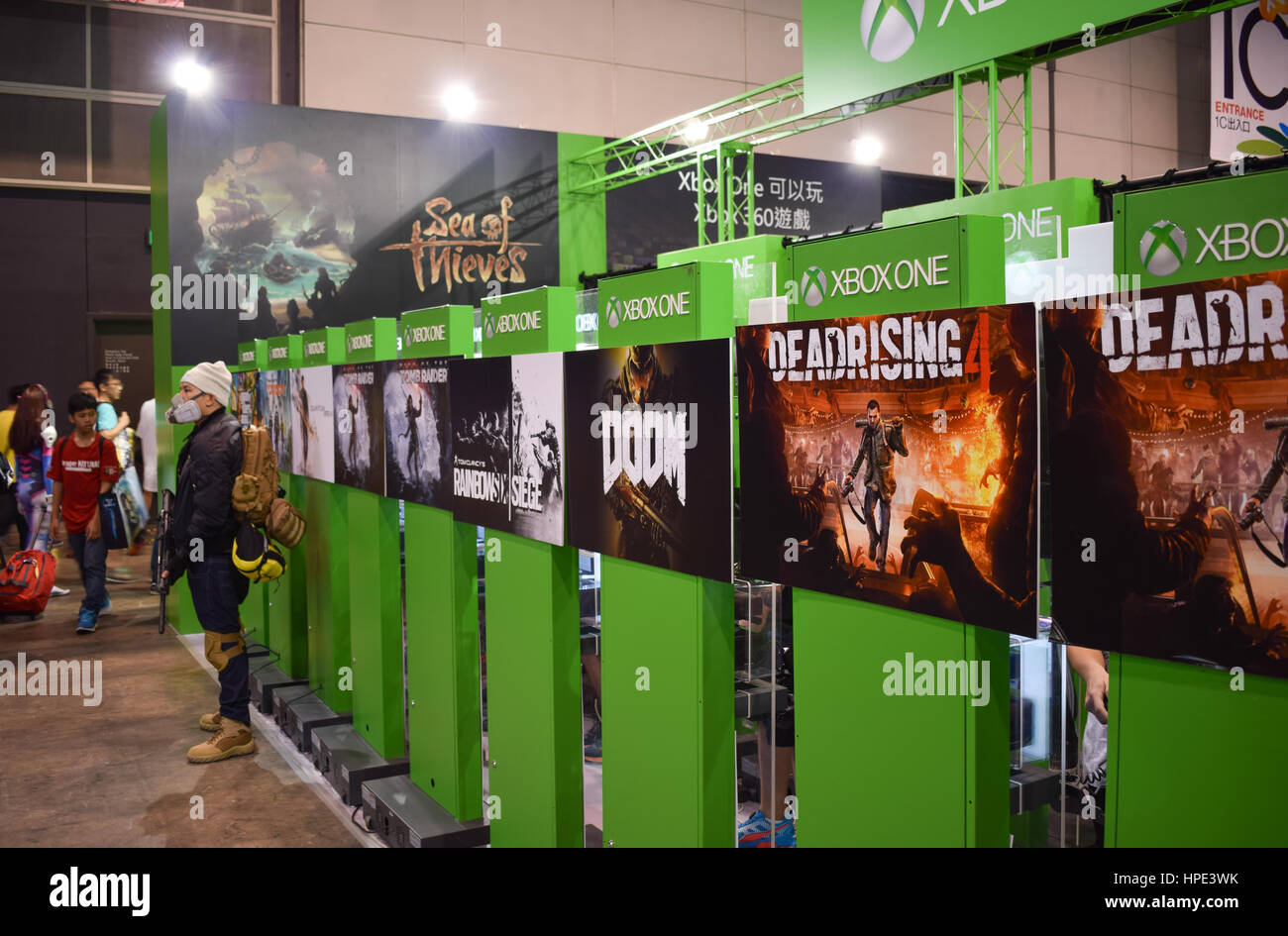 Video game stations, with an Xbox employee dressed in post-apocalyptic gear, at a game expo in Hong Kong - Stock Image