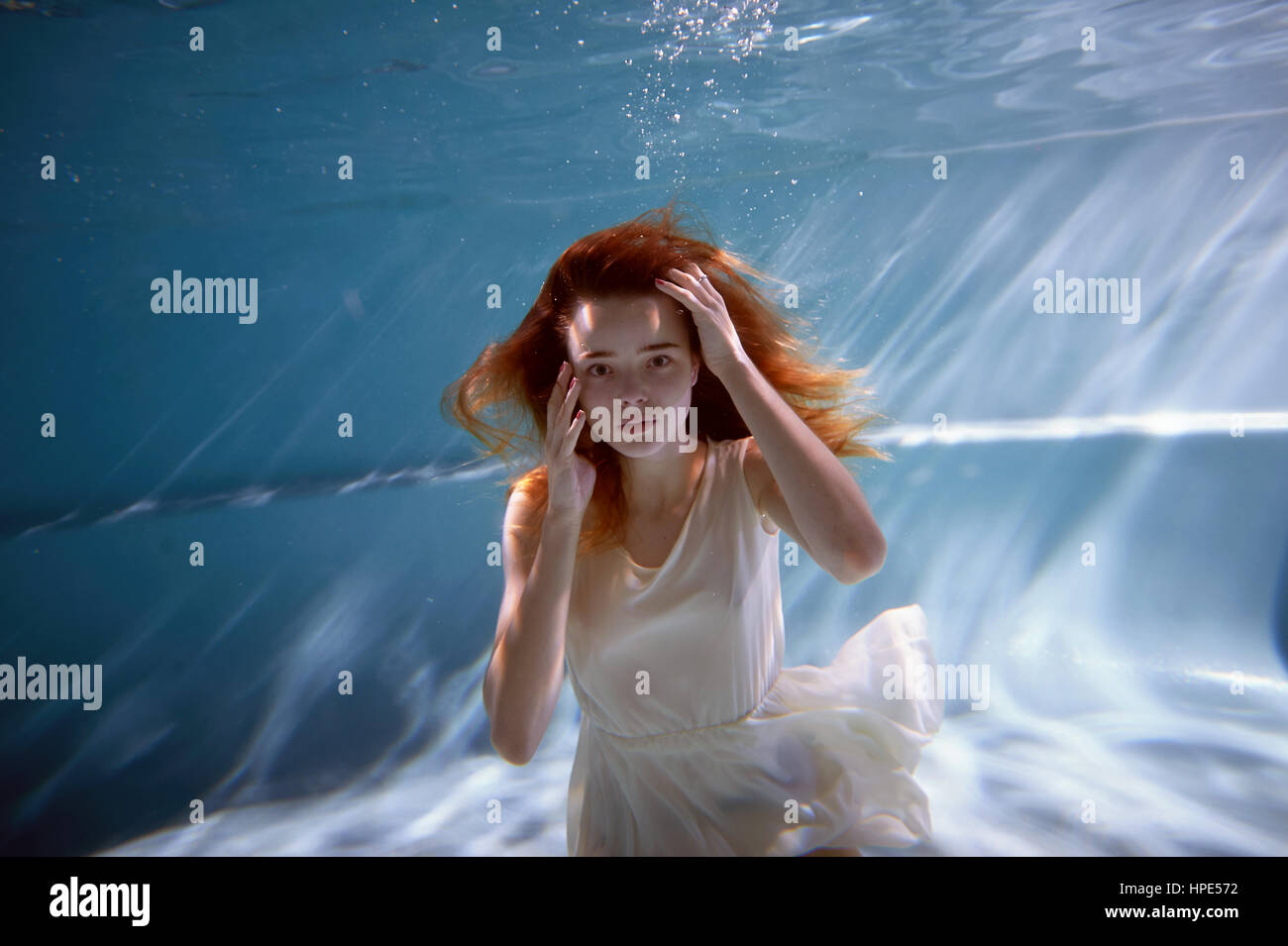 Underwater in the pool with the purest water. Beautiful girl in a scarlet dress and flowing hair. Stock Photo