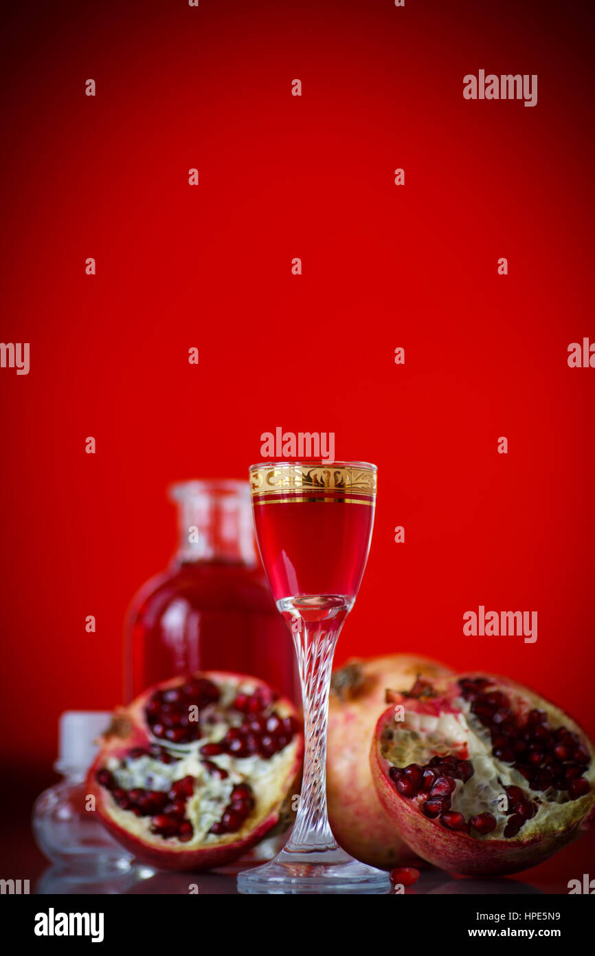 sweet pomegranate alcoholic cordial in the decanter with a glass on a red background - Stock Image
