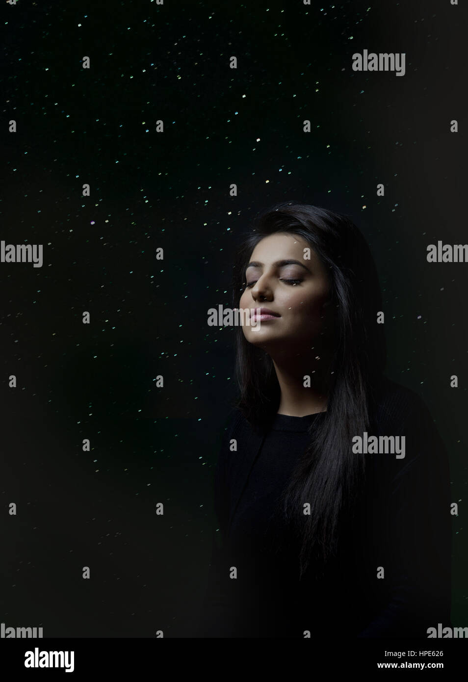 Woman thinking with closed eyes in digitally composed glowing lights or starry sky - Stock Image