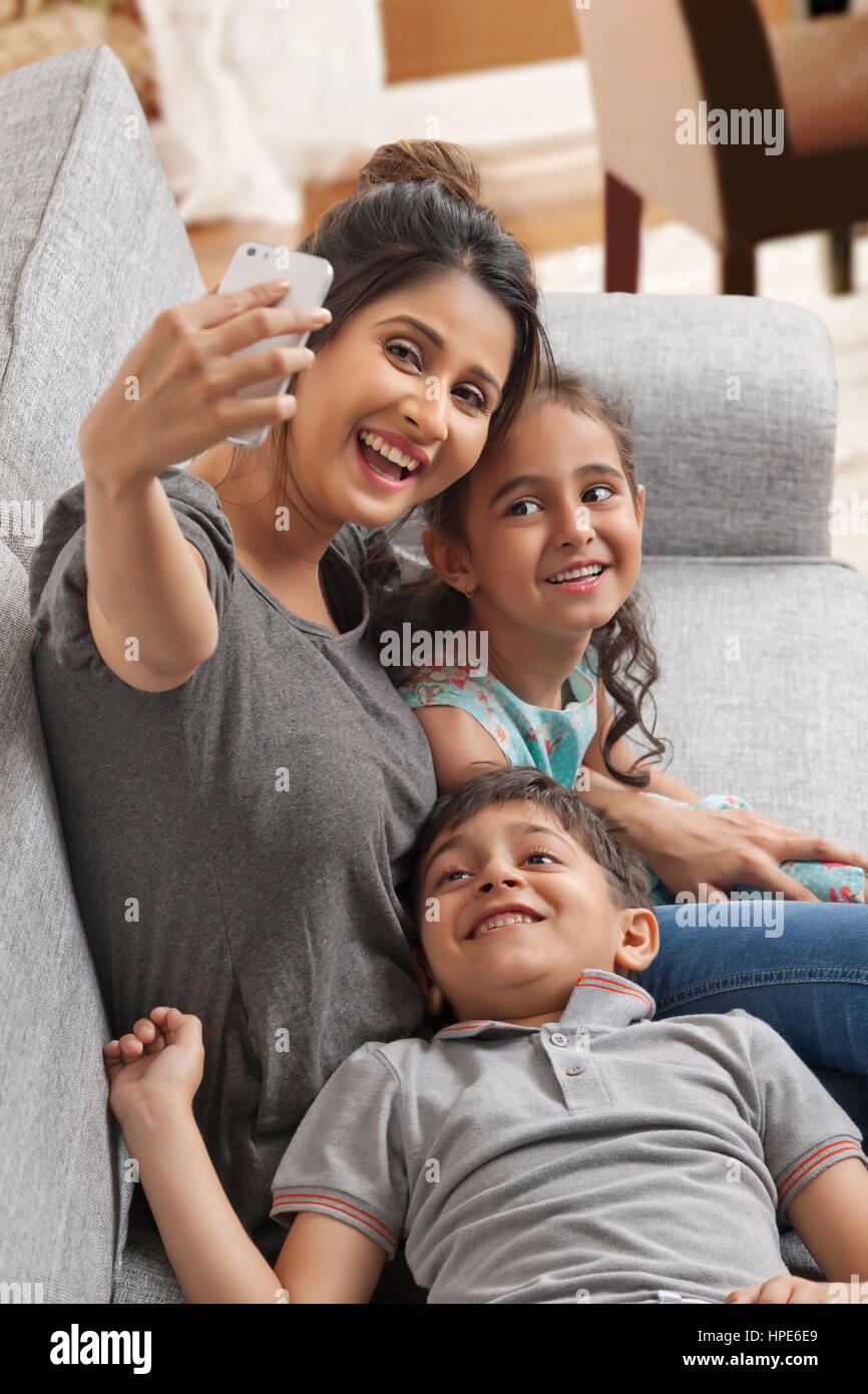Smiling mother takes selfie with her children - Stock Image