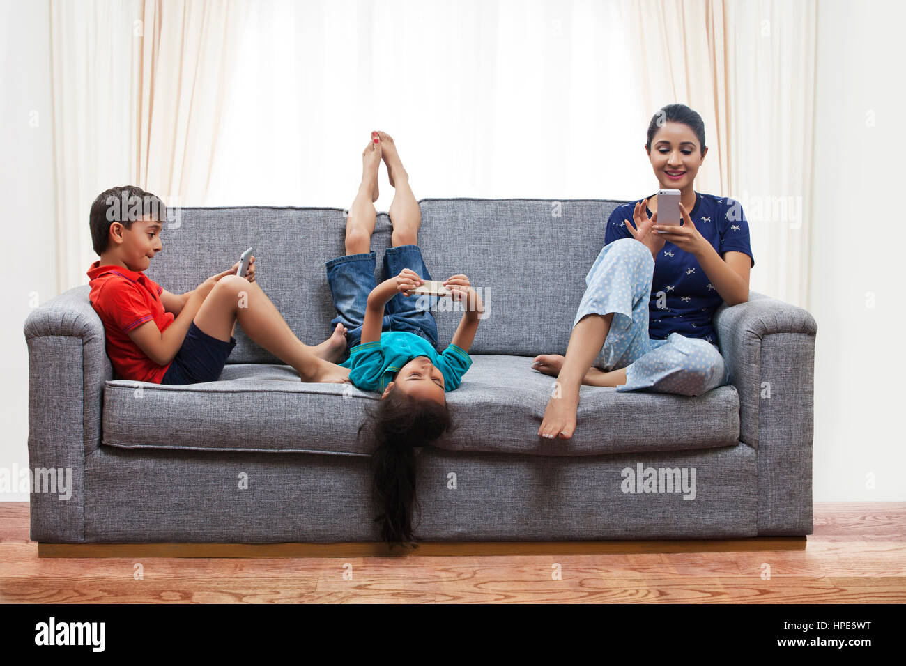 Mother and her children using cell phones on sofa in living room - Stock Image