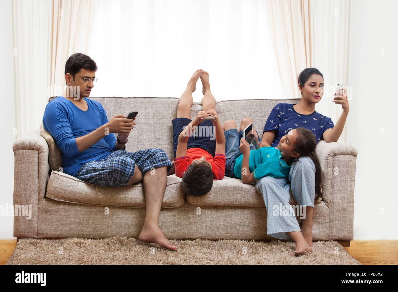 Family using cell phones and digital tablets in living room - Stock Image