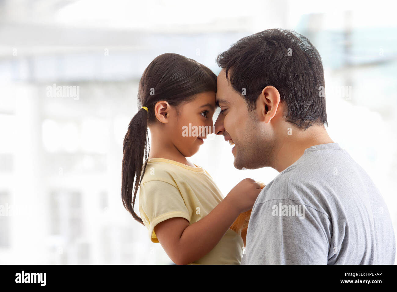 Father and daughter rubbing noses together - Stock Image