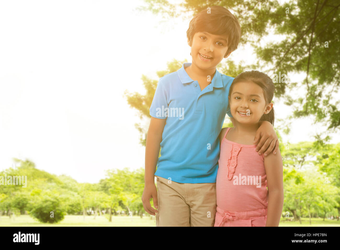 Portrait of brother and sister standing arm around in park - Stock Image