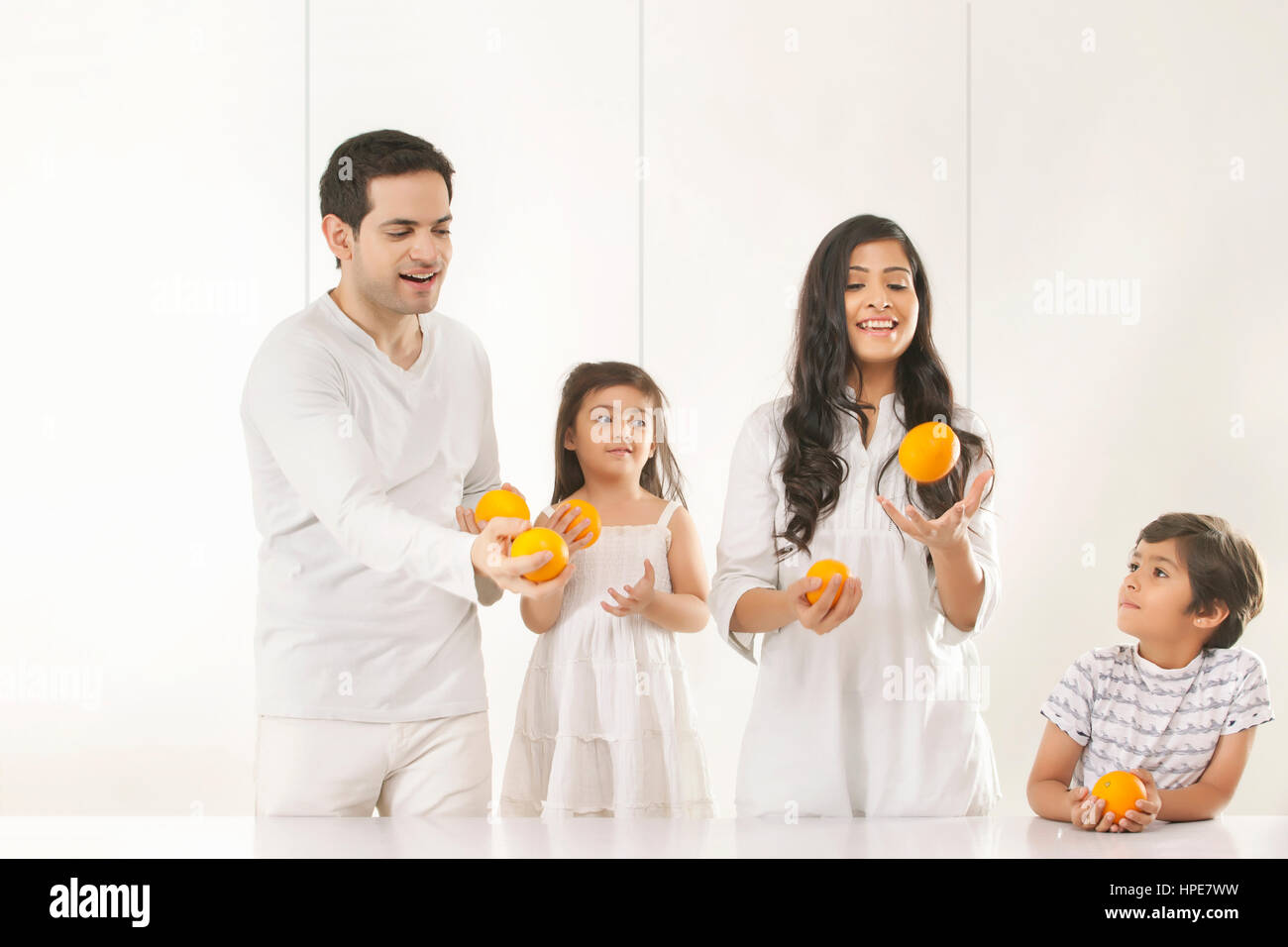 Family juggling with oranges - Stock Image