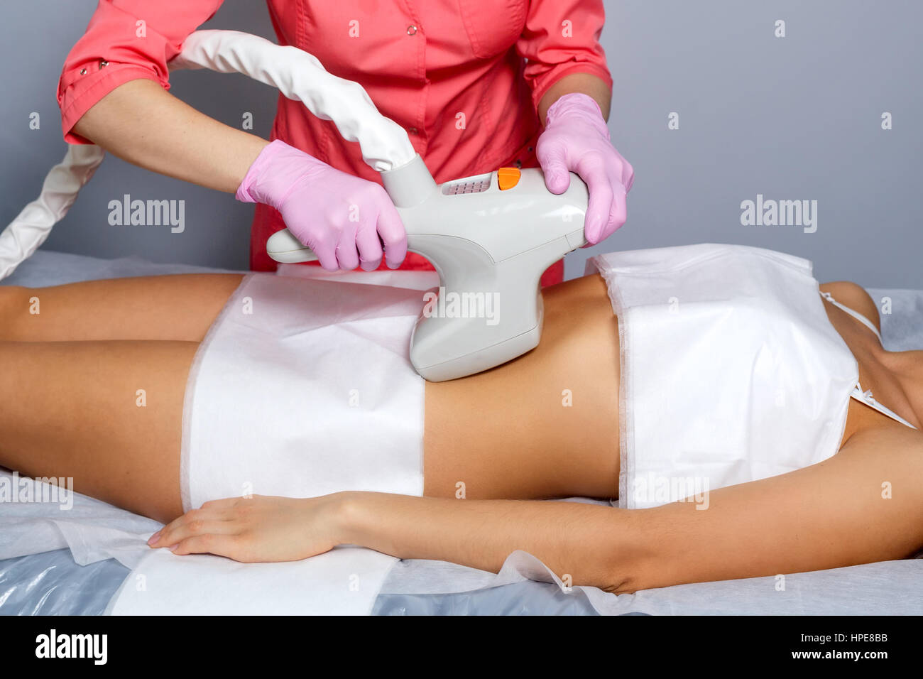 Vacuum massage of the abdomen of a young girl. Instrumental cosmetology. Spa Studio. Rejuvenation and skin tightening. - Stock Image