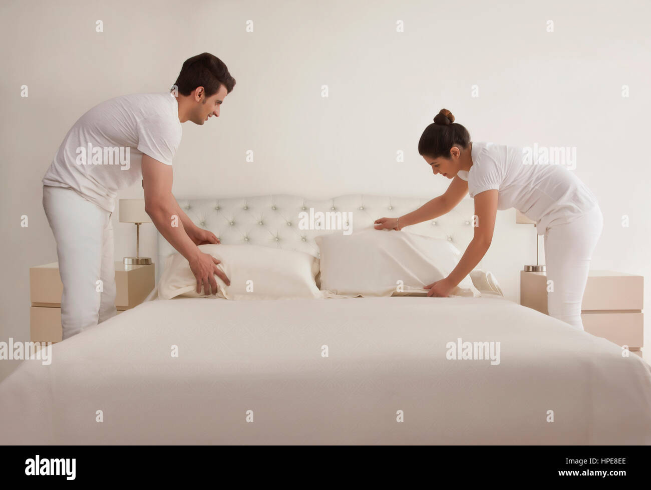 Young couple making bed - Stock Image