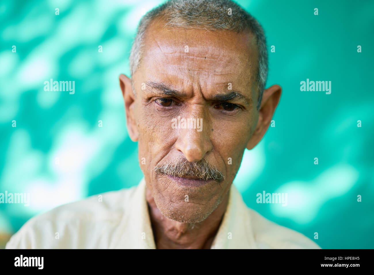 Real Cuban people and emotions, portrait of sad old latino man from Havana, Cuba looking down with worried face - Stock Image