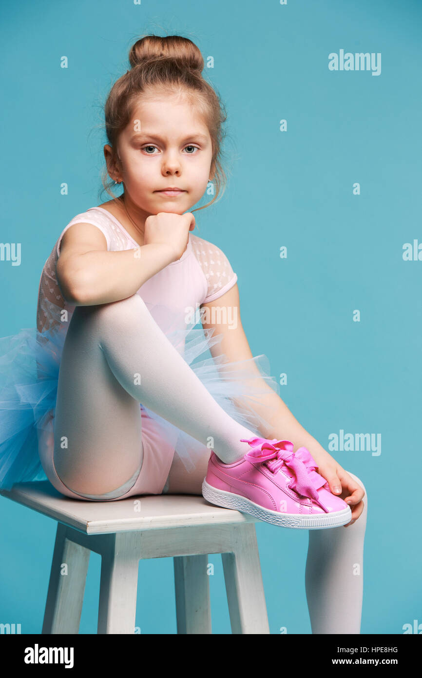 6a107e9f8ce8 The little girl as balerina dancer sitting on white wooden chair at ...