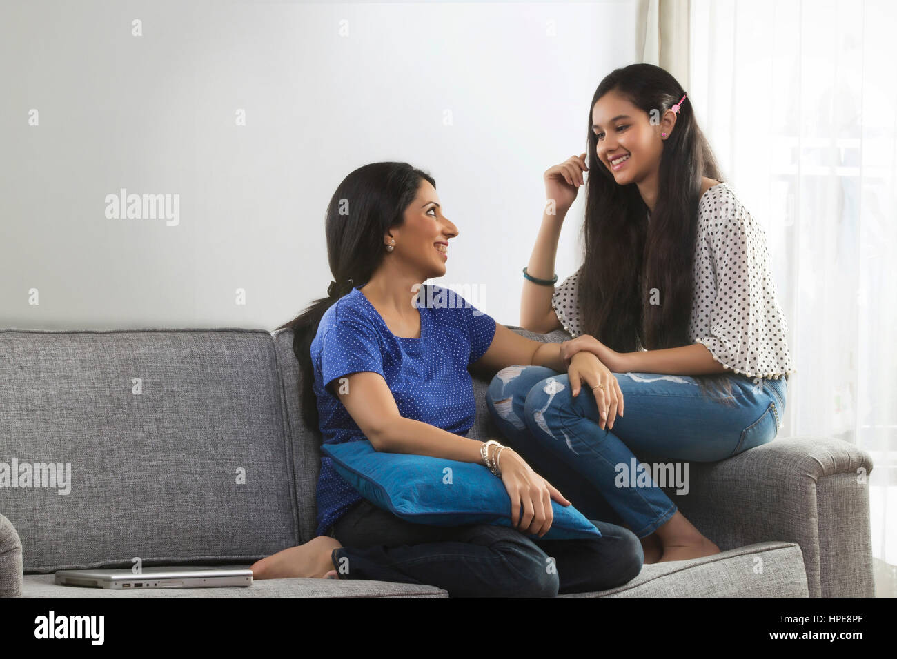 Smiling mother and teenage daughter conversing in living room - Stock Image