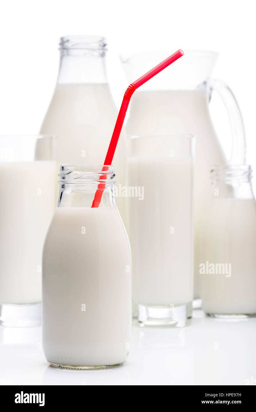 milk bottle with red drinking straw and other milk glasses on background - Stock Image