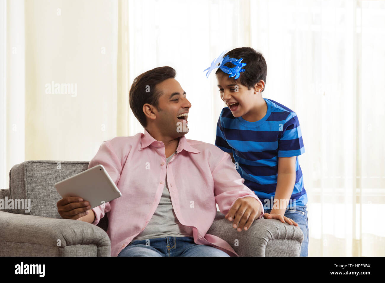 Boy with mask laughing with his father looking at each other - Stock Image
