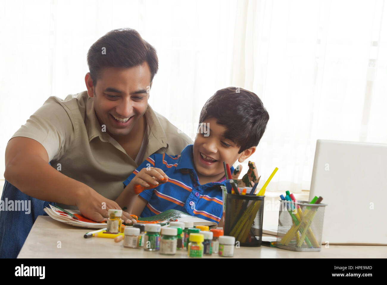 Father and son finger painting together - Stock Image