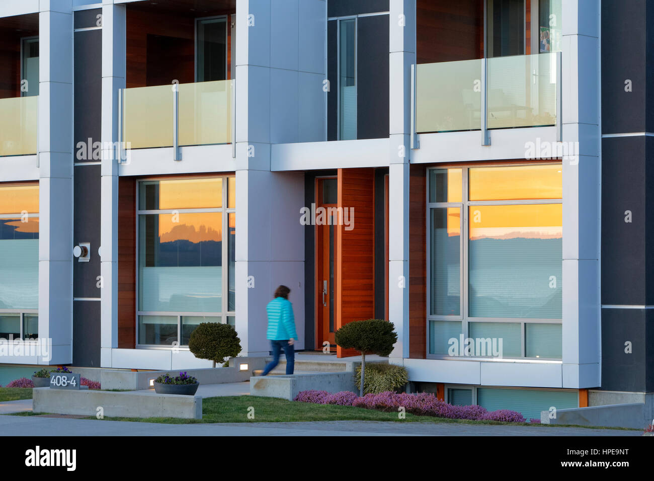 Woman entering home along waterfront lit up with sunset afterglow-Victoria, British Columbia, Canada. - Stock Image