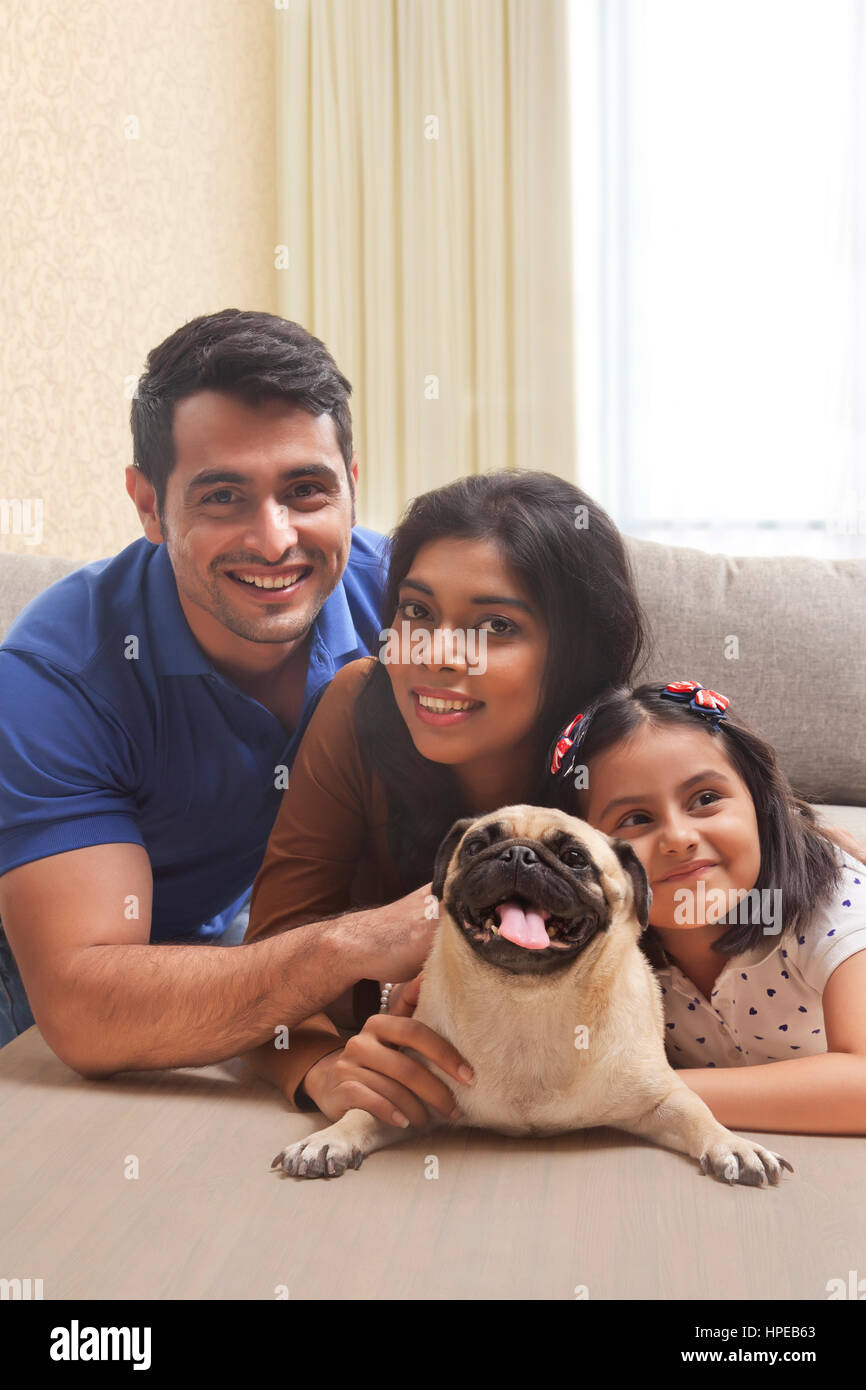 Portrait of smiling family with daughter and pug - Stock Image