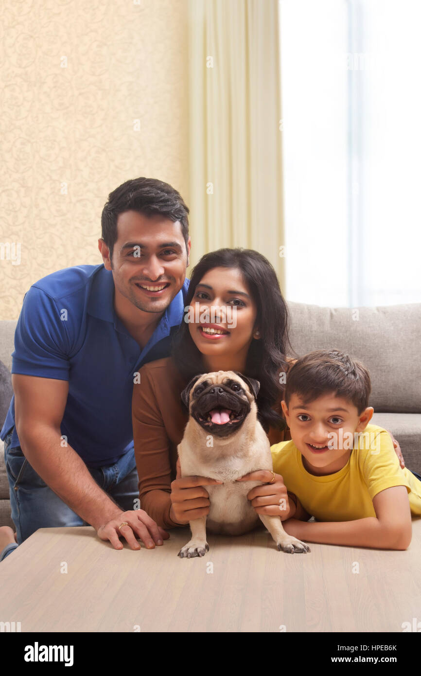 Portrait of smiling family with son and pug - Stock Image