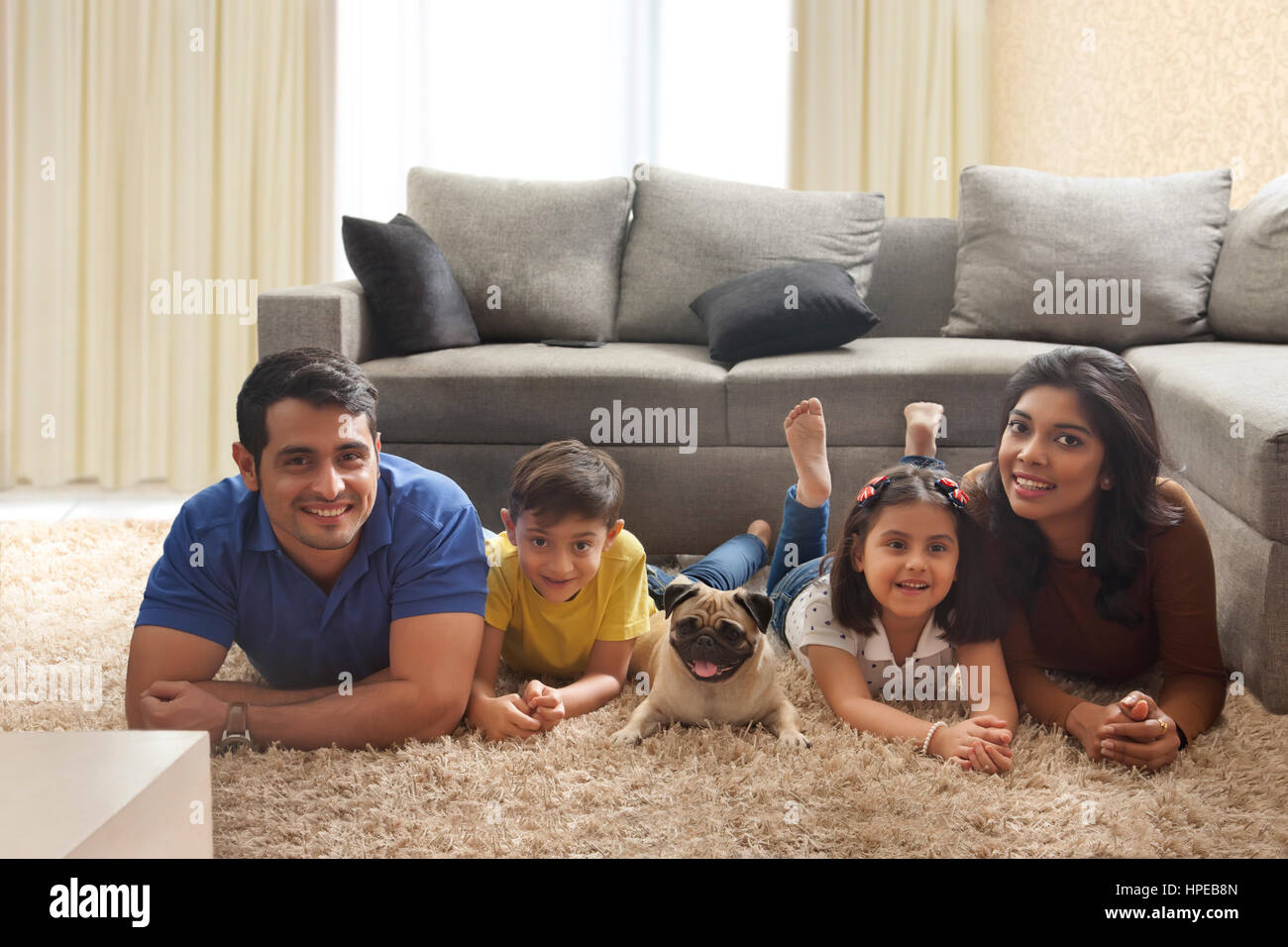 Happy family with pug posing on carpet in living room - Stock Image