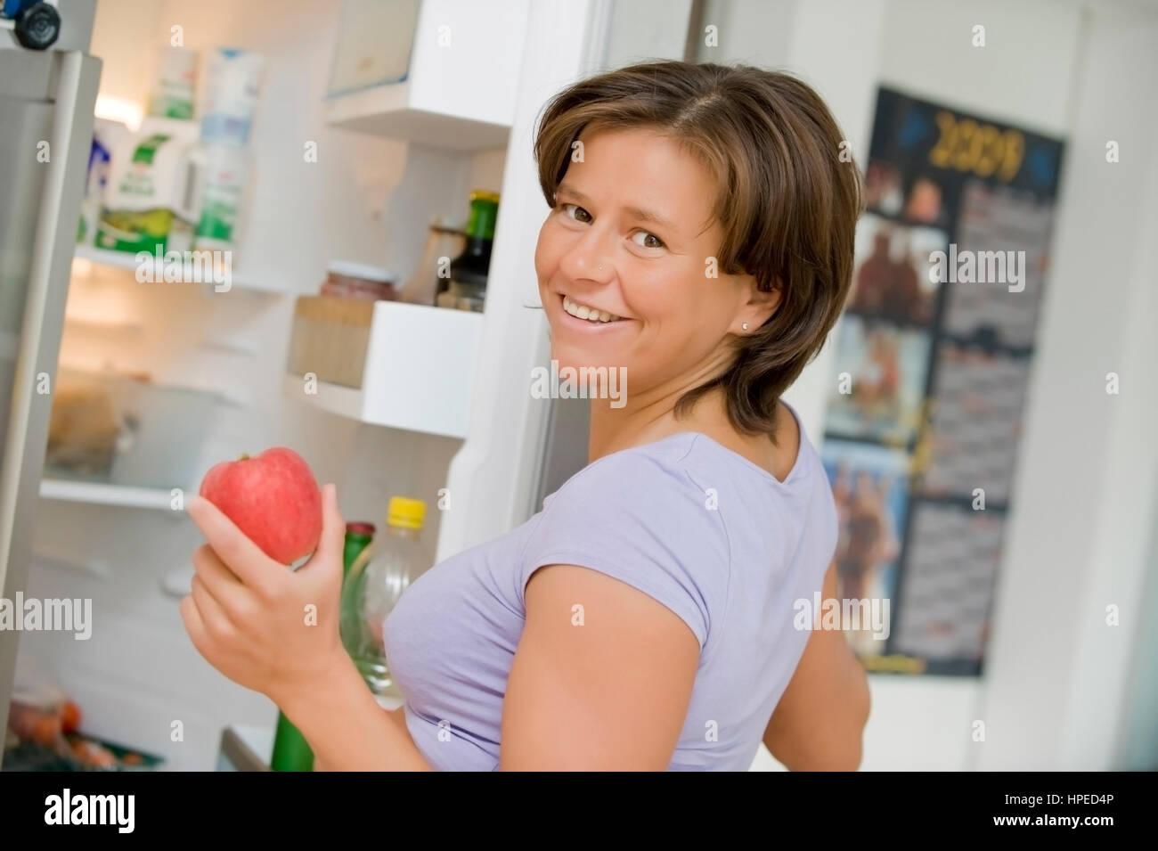 Model released , Junge, lachende Frau nimmt Apfel aus dem Kuehlschrank - woman with an apple in hand - Stock Image