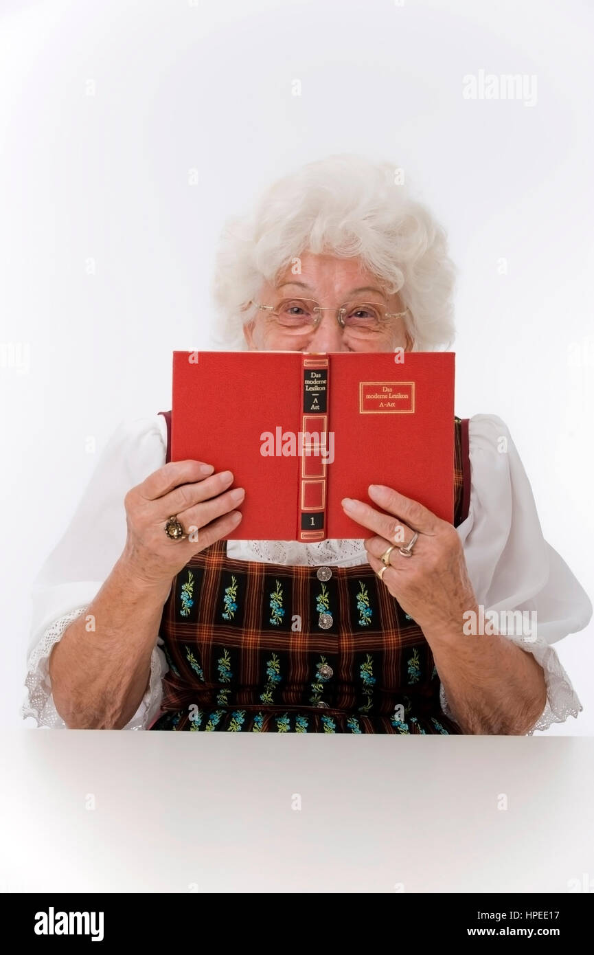 Model released , Seniorin versteckt sich hinter Lexikon - older woman with lexicon - Stock Image